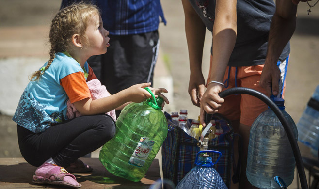 Sonya, 4, watching as her brother collects water at a pumping station in Slovyansk, a city gripped by shortages.