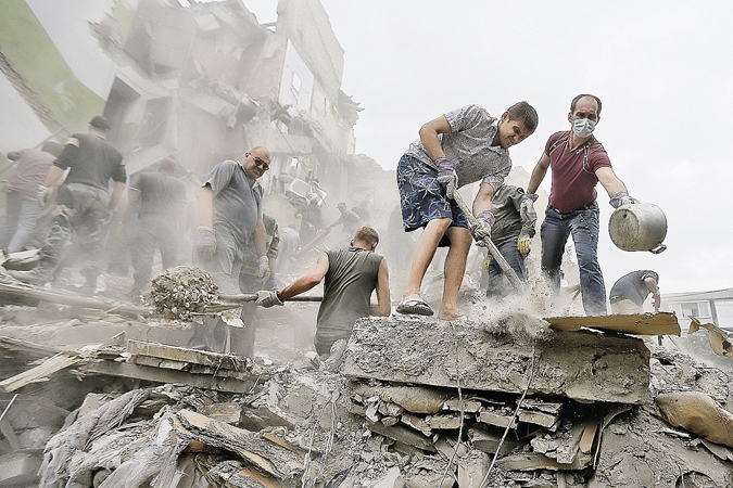ITAR-TASS: DONETSK REGION, UKRAINE. JULY 15, 2014. Local residents clear rubble in a residential area of the town of Snezhnoye in the aftermath of a shelling attack by the Ukrainian government's forces. (Photo: ITAR-TASS/ Zurab Dzhavakhadze)